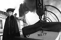 Old woman standing on the deck of a steamship next to lifeboat with smokestacks in the background, circa 1930's.   (photo: www.bcpix.com)