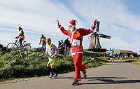 Nederland Zaanse Schans. Deelnemers aan de Zaanse Schansloop. De Zaanse Schansloop gaat door de Kalverpolder en langs de molens. Foto Berlinda van Dam / Hollandse Hoogte. Man loopt verkleed als kerstman om reclame te maken voor de komende Santa Run in Zaandijk