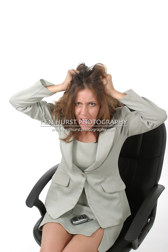Frustrated executive business woman with a troubled expression sitting in her office chair pulling her hair out.