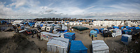 """Calais Jungle Camp (On the right) the containers' """"new camp"""" protected by high fences, security guards and finger prints reader at the gate used as the """"key"""" to enter.<br /> <br /> Calais Jungle Camp.<br /> <br /> Under the Sky of Calais & Dunkirk. Two Camps, Two Sides of the Same Coin: Not 'migrants', Not 'refugees', just Humans.<br /> <br /> France, 24-30/03/2016. Documenting (and following) Zekra and her experience in the two French camps at the gate of the United Kingdom: Calais' """"Jungle"""" and Dunkirk's """"Grande-Synthe"""". Zekra lives in London but she is originally from Basra in Iraq. Zekra and her family had to flee Kuwait - where they moved for working reason - due to the """"Gulf War"""", and to the Western Countries' will to """"export Democracy in Iraq"""". Zekra is a self-motivated volunteer and founder of """"Happy Ravers"""", a group of people (not a NGO or a charity) linked to each other because of their love for rave parties but also men and women who meet up every week to help homeless people and other people in need in Central London. (Here there are some of the stories I covered about Zekra and """"Happy Ravers"""": http://bit.ly/1XVj1Cg & http://bit.ly/24kcGQz & http://bit.ly/1TY0dPO). Zekra worked as an English teacher in the adult school at Dunkirk's """"Grande-Synthe"""" camp and as a cultural mediator and Arabic translator for two medic teams in Calais' """"Jungle"""". Please read her story at the beginning of this reportage."""