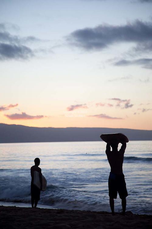 Skimboarders at sunset at Ka'anapali Beach on West Maui