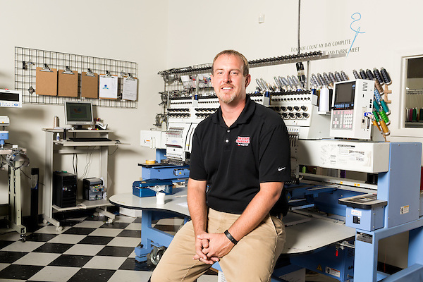 September 18, 2014. Raleigh, North Carolina.<br />  Chuck Sawyer poses for a portrait in front of the embroidery machine at his main retail and production franchise.<br />  Chuck Sawyer, 37, is the owner of three Instant Imprints franchises, specializing in promotional materials such as t-shirts,signs and mugs. Sawyer wishes he had more saved for retirement and is encouraging his none employees to start thinking about how they will save for when they get older.<br /> Publication: AARP Bulletin<br /> Editor: Jenna Isaacson-Fuller<br /> Model Released<br /> Portrait