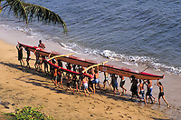 Many children and teenagers carry large yellow outrigger canoe up sand from edge of ocean; crosslit. Kihei Hawaii, Maui.