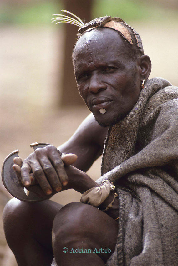 A Turkana man and traditional headress. On his wrist is a circular knife used for cutting meat and occasionally in combat.