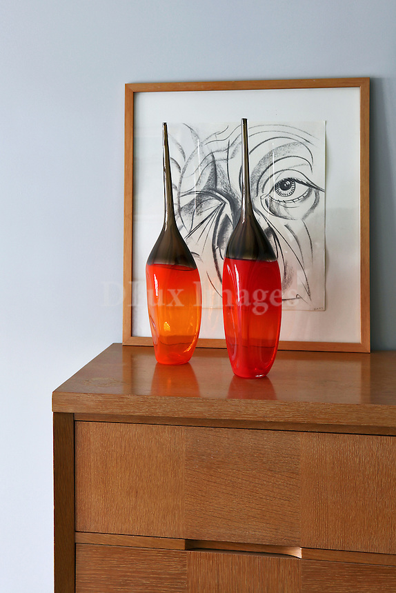 red vases on a wooden cabinet