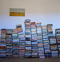 Books for holiday reading are stacked in crooked piles against a wall of the bedroom