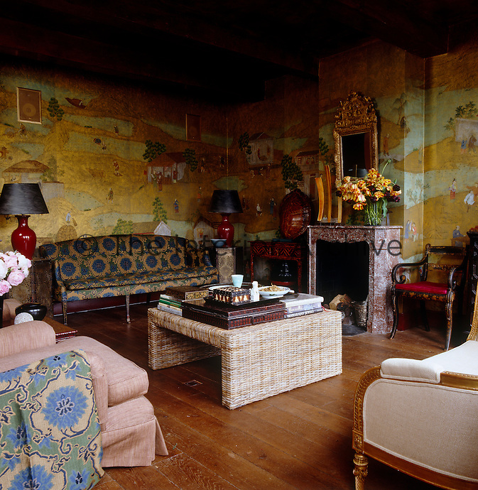 Golden wallpaper depicting rural Chinese scenes covers the walls of this living room which is furnished with an eclectic selection of furniture, fabrics and objects