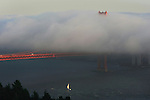 Th San Francisco fog creeps over the deck of the Golden Gate Bridge as a cruise ship sails out at dusk in San Francisco Calif., on September 23, 2009.