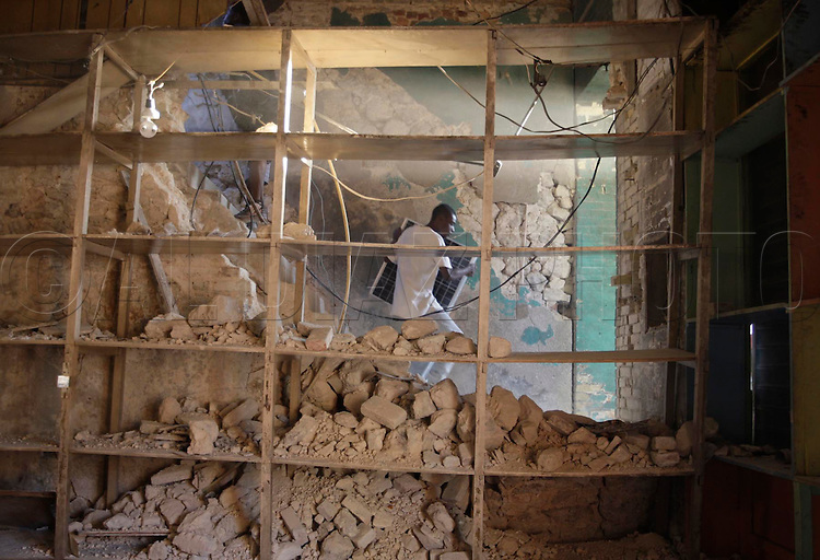 Earthquake aftermath in Port-Au-Prince, Haiti, on January 20, 2010..A looter is seen carrying goods out of a building in downtown Port-Au-Prince..