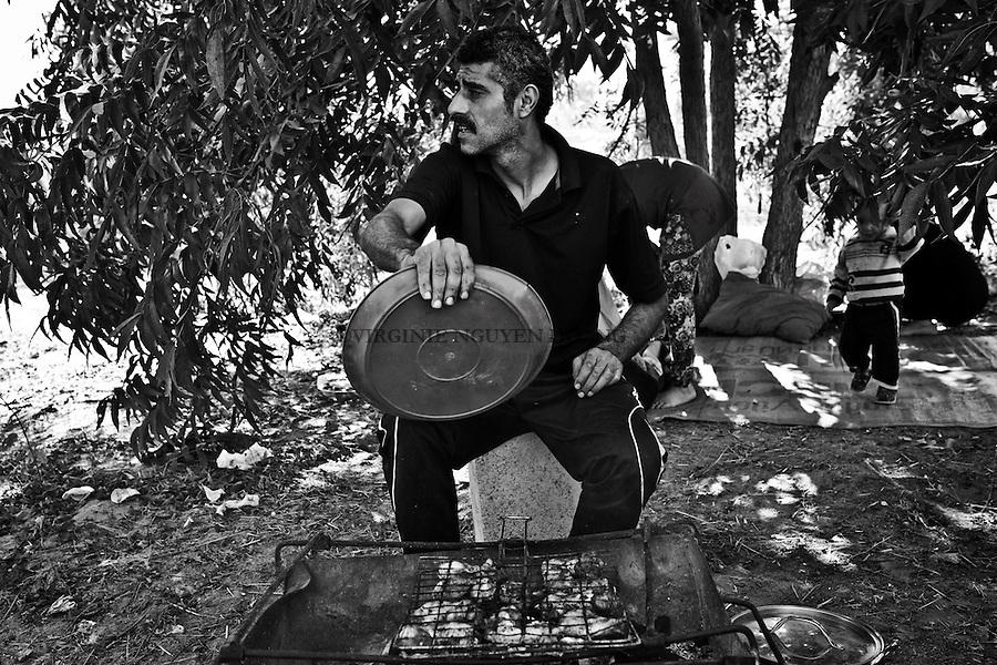 Gaza, Beit Hanoun: Shady cuit des cuisses de poulet sur son barbecue. Depuis la guerre c'est la premi&egrave;re fois qu'il se rend dans sa terre car il avait peur d'&ecirc;tre bombard&eacute; ou que ses enfants marchent sur une bombe non explos&eacute;e &laquo;Je ne me sens pas en s&eacute;curit&eacute; ici car nous sommes &agrave; la fronti&egrave;re avec Isra&euml;l, mais mes enfants n'arr&ecirc;tent pas de me demander ...&raquo;, dit Shady.<br /> <br /> Gaza, Beit Hanoun: Shady is cooking some chicken legs on his barbecue. Since the war it's the first time that he came to his land as he was scared of being bombed or that his children walk on a remains of a bomb. &quot;I  don't feel safe being here as it's the border with Israel but my children keep asking all the time...&quot; says Shady.