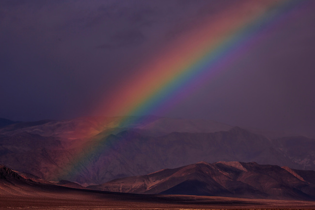 A bright rainbow appears over Eureka Valley at Death Valley National Park, California