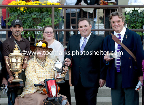 Phyllis Wyeth, seated, poses with Champagne trophy following Union Rags victory. At far right is her husband, renowed American artist Jamie Wyeth.