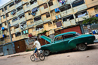 "A young Cuban man rides a bicycle in front of the huge apartment blocks in Alamar, a public housing periphery of Havana, Cuba, 9 February 2011. The Cuban economic transformation (after the revolution in 1959) has changed the housing status in Cuba from a consumer commodity into a social right. In 1970s, to overcome the serious housing shortage, the Cuban state took over the Soviet Union concept of social housing. Using prefabricated panel factories, donated to Cuba by Soviets, huge public housing complexes have risen in the outskirts of Cuban towns. Although these mass housing settlements provided habitation to many families, they often lack infrastructure, culture, shops, services and well-maintained public spaces. Many local residents have no feeling of belonging and inspite of living on a tropical island, they claim to be ""living in Siberia""."