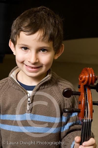 Elementary School New York male kindergarten student arts enrichment music boy posing with cello vertical