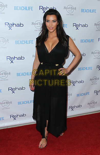 Kim Kardashian.hosts Rehab Sunday at Paradise Beach at the Hard Rock Hotel and Casino, Las Vegas, Nevada, USA..3rd June 2012 .full length black dress sheer cleavage belt hand on hip.CAP/ADM/MJT.© MJT/AdMedia/Capital Pictures.