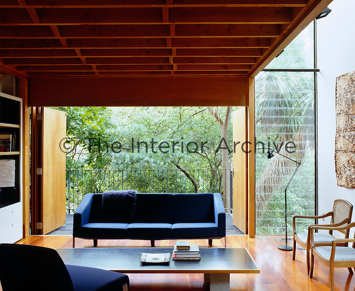 The folding doors and double-height louvered windows allow the surrounding landscape to become part of the living room
