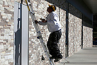 NWA Media/DAVID GOTTSCHALK - 12/15/14 -  Mario Lanzano, with Deihl Enterprises, moves into position Monday December 15, 2014 to replace a piece of stone on the facade above one of the doorways on the south side of the Fayetteville High School Performing Arts Center.