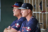 Manager Randy Ingle (12), left, and coach Barrett Kleinknecht (25) of the Rome Braves watch from the dugout during a game against the Greenville Drive on Tuesday, August 30, 2016, at Fluor Field at the West End in Greenville, South Carolina. Greenville won, 7-3. (Tom Priddy/Four Seam Images)