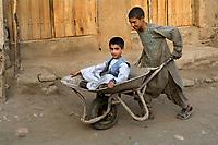 Boy in wheelbarrow.