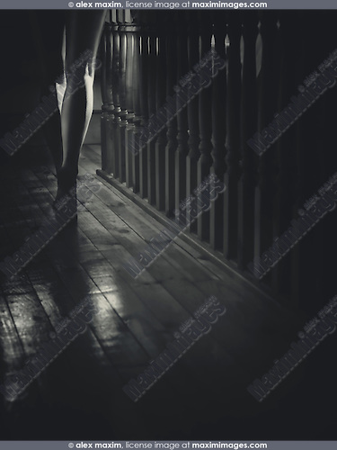 Closeup of bare legs of a woman walking barefoot on a staircase of a dark house Black and white