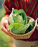 JAPAN, Kyushu, woman holding freshly picked garden vegetables