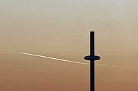 An aeroplane leaves a vapour trail as it flies over the British Airways i360 in Brighton, East Sussex, England UK. Saturday 24 February 2018
