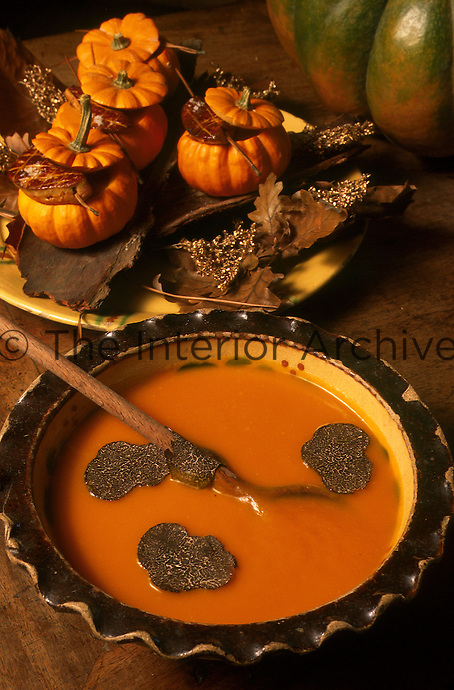 Close up of a bowl of pumpkin soup served with slices of fresh truffle