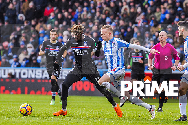 Crystal Palace's midfielder Wilfried Zaha (11) holds off Huddersfield Town's defender Florent Hadergjonaj (33) during the EPL - Premier League match between Huddersfield Town and Crystal Palace at the John Smith's Stadium, Huddersfield, England on 17 March 2018. Photo by Stephen Buckley / PRiME Media Images.