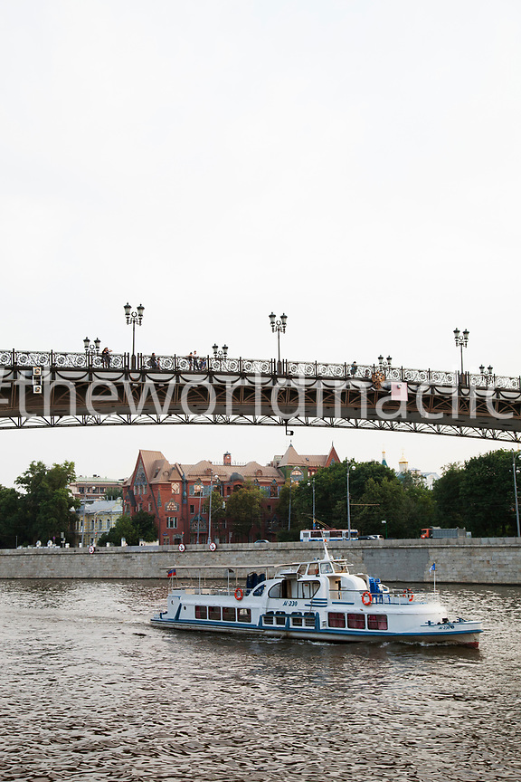 RUSSIA, Moscow. A ferry passes under the Patriarshy Bridge on the Moscow River.