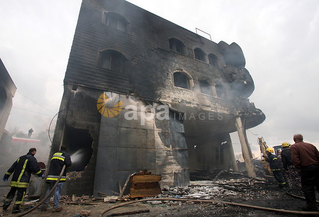 Palestinian civil defense forces try to stop fire burning in carpentry workshop and a factory for plastic materials, in the area of Doha, near the biblical town of Bethlehem, on February 13, 2011. Photo by Najeh Hashlamoun