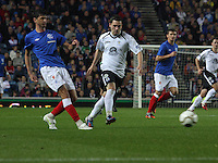 Emilson Cribari passes under pressure from Nicky Clark in the Rangers v Queen of the South Quarter Final match in the Ramsdens Cup played at Ibrox Stadium, Glasgow on 18.9.12.