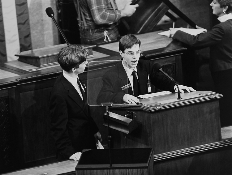 Two pages take the podium after State of Union address as a workman takes chair away from behind on Jan. 30, 1992. (Photo by Laura Patterson/CQ Roll Call via Getty Images)