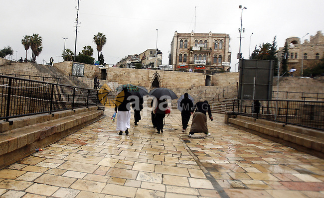 Palestinians walk in front of the Dome of the Rock on the compound know to Muslims as al-Haram al-Sharif during stormy weather in Jerusalem's Old City January 7, 2013. Photo by Mahfouz Abu Turk