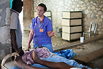 Project HOPE volunteer nurse Nora Sheehan talks with the relative of a cholera patient at the Hospital Albert Schweitzer on Thursday, October 28, 2010 in Deschapelles, Haiti.