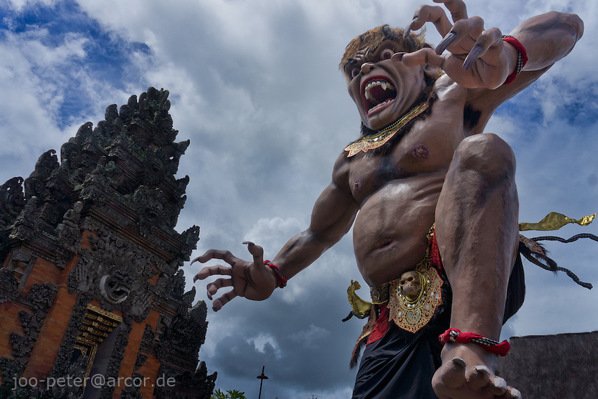 Ogoh-Ogoh (demon) sculpture, character Bhuta Tetajan (demon of gambling, cockfight), designed by Kan Kulak, made by banjar  in Pelihatan, in front of Pura /temple,  elihatan,Central Bali. Balinese New Year called Nyepi (around march according to lunar calendar),  is a silent day of meditation and spiritual purification. One day before exorcist rituals are held for purification and balance of polar powers of the universe, first at noon by a priest (exorcism called Caru or Tawur Agung) and later on after sunset in a popular, carneval-like procession of Ogoh-Ogoh, symbolizing bhuta kali (demon, bad spirits,bad habits),  so all the bad spirits leave the village and the island.  Loud, rhythmic music and special performances are part of the procession called Ngerupuk. Road crossings are major spots of exorcism and special ogoh-ogoh performance, since demons often like to dwell here. At Nyepi, the following day, there is 24 hours silence, no vehicle or people on the street, no light or fire, no working - all the bad spirits should think, the island is abandoned and leave the island. Day after Nyepi is a day of reconciliation - new year starts purified.