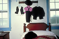 Typical clothing of an Amish boy hang in a child's bedroom which is simply furnished with no decorative curtains or closets. Amish. Lancaster Pennsylvania United States Amish homestead.