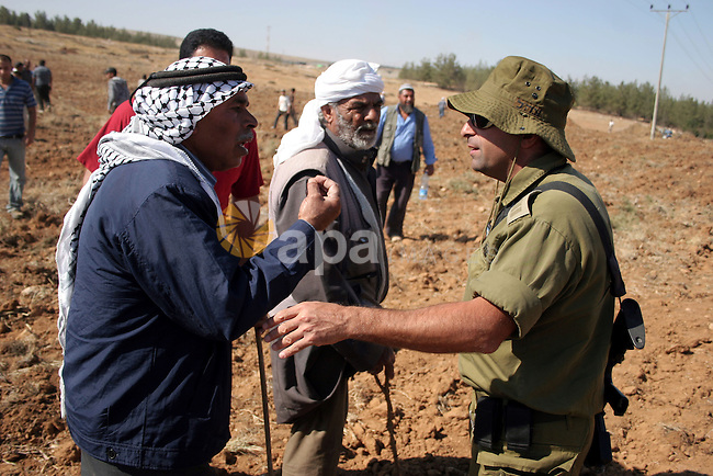 Palestinian farmers work at their land as Israeli border guards prepare to evacuate Jewish settlers who tried to make a sit-in on a Palestinian land that was being cultivated by farmers, on July 1, 2011, in the West Bank village of Yatta, near the Israeli settlement of Sosia. Photo by Najeh Hashlamoun ......