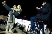 Kandahar, Afghanistan - December 17, 2009 -- Comedian Dave Attell and tennis star Anna Kournikova perform at the 2009 USO Holiday Tour stop in Kandahar, Afghanistan, Thursday, December 17, 2009. United States Navy Admiral Mike Mullen, chairman of the Joint Chiefs of Staff, and his wife Deborah, welcomed tennis coach Nicholas Bollettiere and musician Billy Ray Cyrus on the tour visiting troops in Afghanistan, Iraq and Germany. .Mandatory Credit: Chad J. McNeeley - DoD via CNP