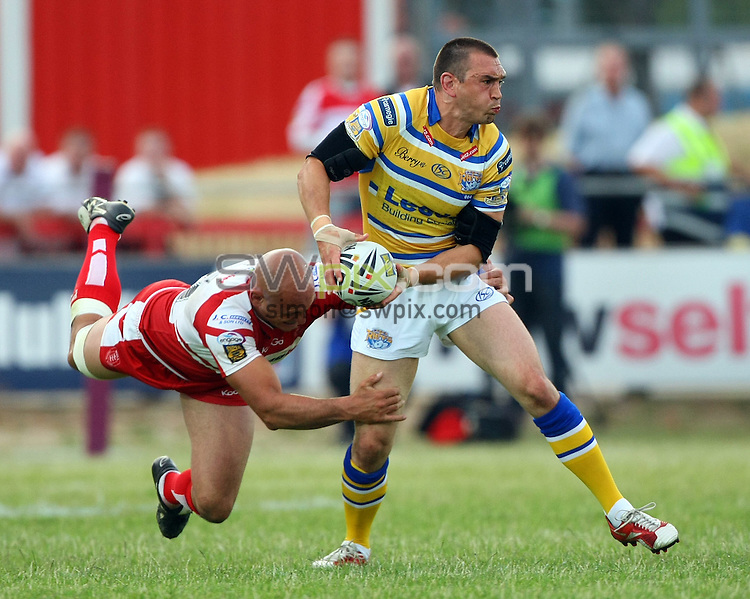 PICTURE BY VAUGHN RIDLEY/SWPIX.COM - Rugby League - Super League - Hull KR v Leeds - Craven Park, Hull, England - 09/07/10...Copyright - Simon Wilkinson - 07811267706...Leeds Kevin Sinfield is tackled by Hull KR's Mick Vella.