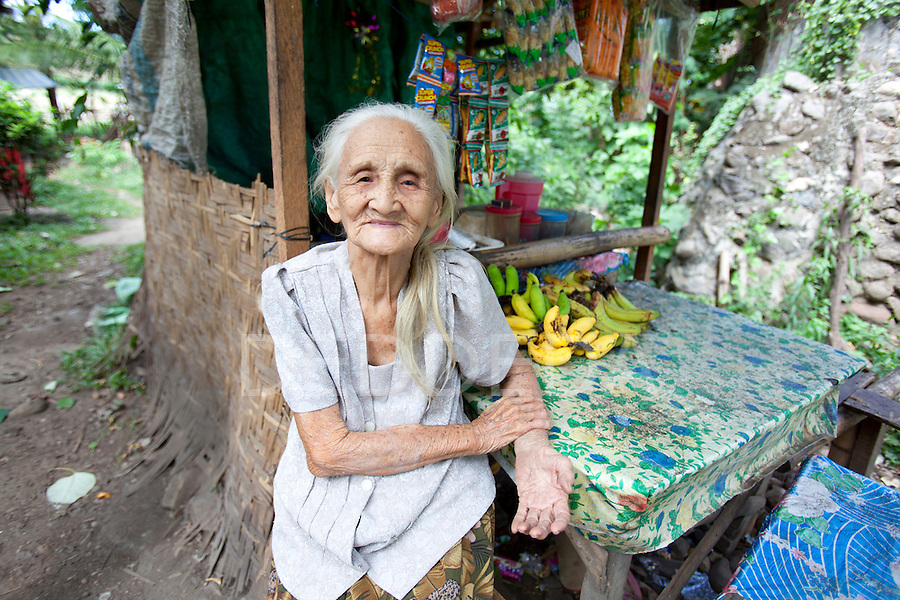 An elderly woman with white hair sits outside her shop where she sells basic goods and fruits and vegetables at her home near Bias City on Negros Island, Philippines.