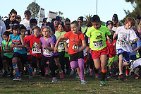 DeAnza Cove, Mission Bay, San Diego CA, USA.  Sunday, January 25 2015:  Participants get underway in the 1-mile kids run part of the Friends of Pacific Beach Schools (FOPBS) School Yard Dash.  The 2nd annual charity event which raises money for the six local schools in the Mission Bay Cluster, comprised of a 1-mile run for kids followed by a 5K run for all ages.  Besides parents, teachers, staff, students and siblings competitors from all over San Diego and abroad ran in the event.  All six schools in the Mission Bay cluster had information booths at the event for potential parents to meet and speak with staff and students.  Music was provided by local teenage band Rubber Band and the string ensemble from Crown Point Elementary School.