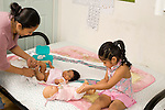 modeling imitation child development 3 year old girl plays with doll as mother changes diaper of newborn baby sister horizotnal Hispanic Mexican American
