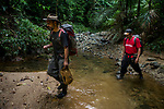 Jaguar (Panthera onca) biologists, Milton Yacelga and Polo Acosta, crossing creek in tropical rainforest, Kaminando Habitat Connectivity Initiative, Mamoni Valley, Panama