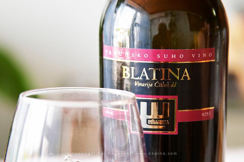 Wine glasses in the tasting room. Bottle of Blatina Vrhunsko Suho Vino red wine. Detail of label with picture of a symbol. Vinarija Citluk winery in Citluk near Mostar, part of Hercegovina Vino, Mostar. Federation Bosne i Hercegovine. Bosnia Herzegovina, Europe.