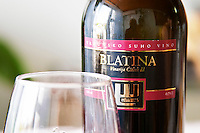 Wine glasses in the tasting room. Bottle of Blatina Vrhunsko Suho Vino red wine. Detail of label with picture of a symbol. Vinarija Citluk winery in Citluk near Mostar, part of Hercegovina Vino, Mostar. Federation Bosne i Hercegovine. Bosnia Herzegovina, Europe.