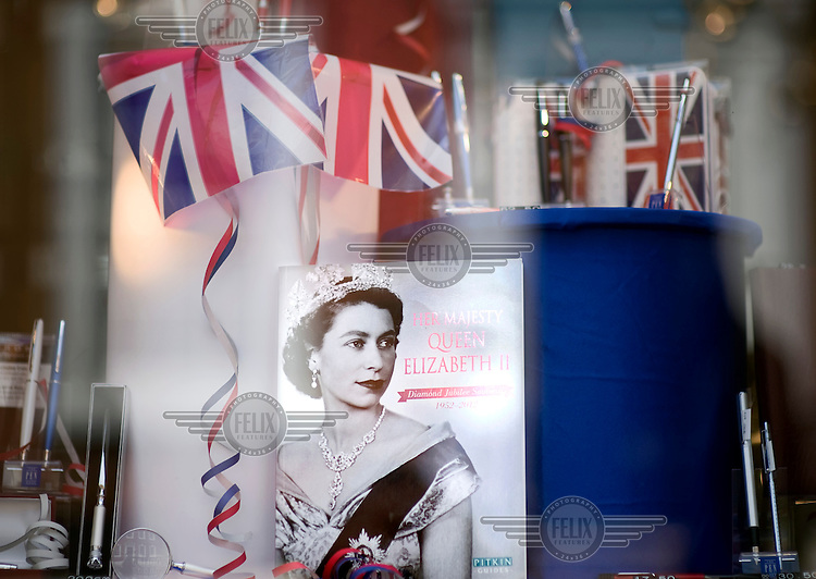 Flags and a book showing the portrait of Queen Elizabeth II are displayed in the window of a shop in Manchester. Queen Elizabeth II is celebrating her diamond jubilee after 60 on the throne. .