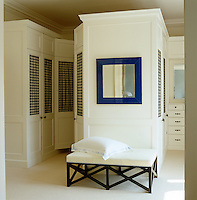 Purpose-built white cupboards furnish this  dressing room which retains its Victorian moulding