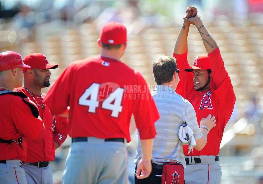 Mar. 14, 2012; Phoenix, AZ, USA; Anaheim Angels pitcher Ervin Santana (right) reacts as he is tended to by a trainer after being hit by a line drive in the second inning against the Chicago White Sox at The Ballpark at Camelback Ranch. Mandatory Credit: Mark J. Rebilas-