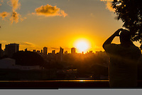 CURITIBA, PR, 06.03.2014 - CLIMA TEMPO / POR-DO-SOL  -  Vista do Fim de tarde desta quinta-feira (06) do bairro alto da XV,  em Curitiba,  ao fundo  paredão de prédios e bairros de Curitiba. Na foto pedestre fazendo foto do por-do-sol. (Foto: Paulo Lisboa / Brazil Photo Press)