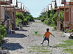 A boy kicks a ball in Camp Corail, a controversial resettlement of earthquake survivors north of Port-au-Prince, Haiti. Thousands of families were relocated to Corail from flood-prone areas of the capital in 2010, yet the promises of jobs that lured them there failed to materialize.